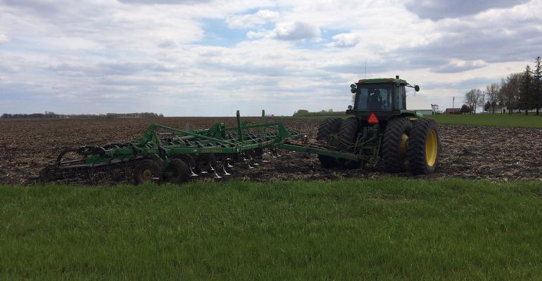 John Deere tractor pulling digger in field.jpg