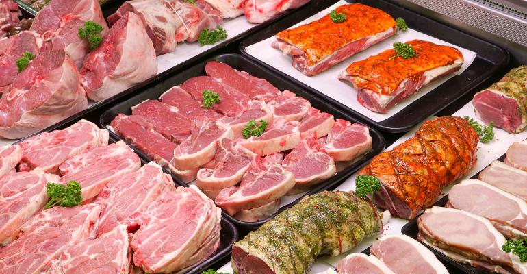 selection of raw meat trays in a butcher display cooler