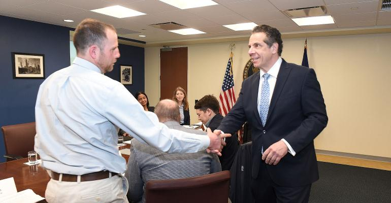 Gov. Cuomo shakes the hand of dairy farmer John Collins
