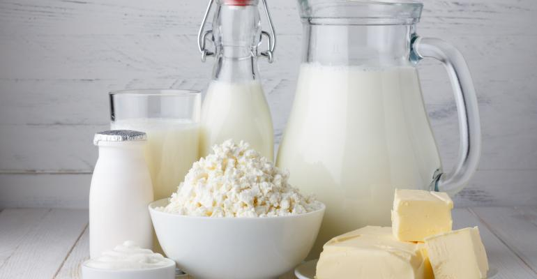 Dairy products including milk, cheese, butter and yogurt displayed on white wood