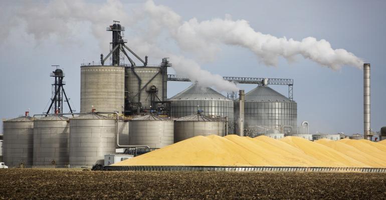 Ethanol plant with pile of corn - iStock483936976.jpg