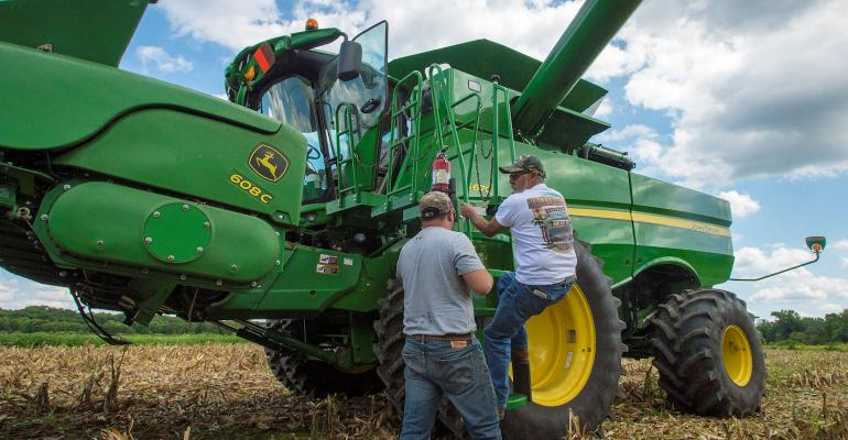 Father and son getting on a combine