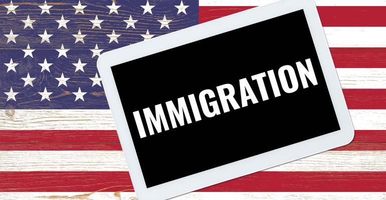 immigration text on tablet pc over us flag painted wooden planks