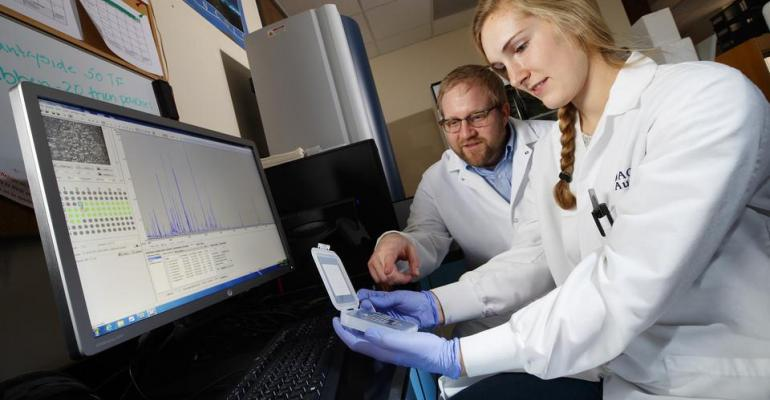 Kara Robbins and Dustin Loy discuss bacteria samples tested in new equipment at the Nebraska Veterinary Diagnostic Clinic.