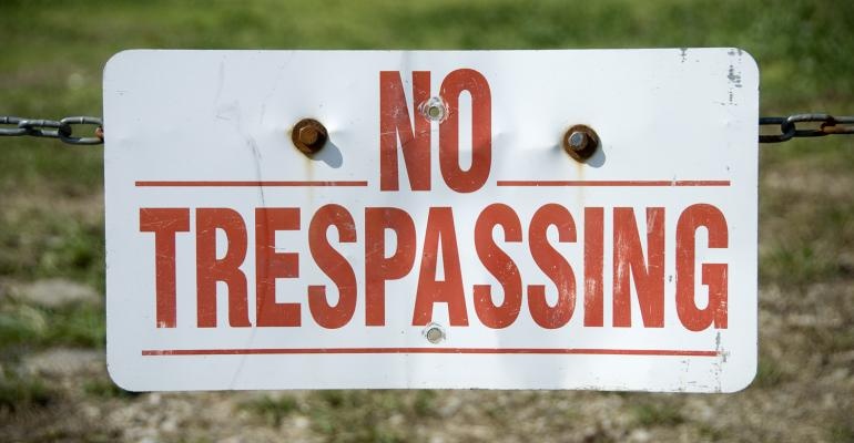 No Trespassing sign on chain in field