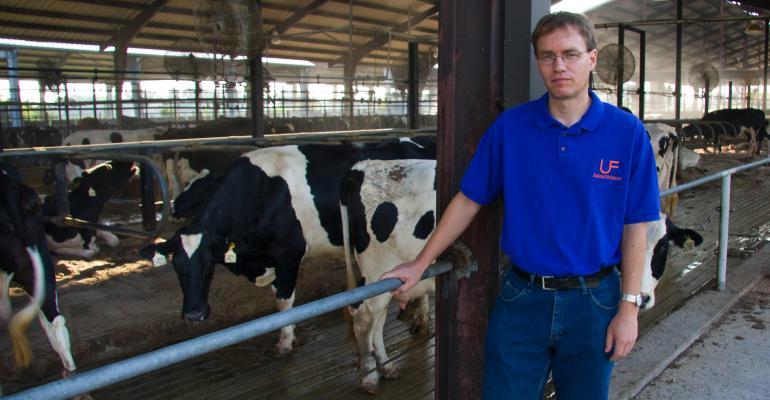Albert De Vries stands next to dairy cow