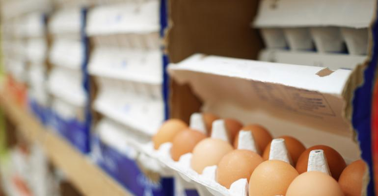 Cartons of eggs in grocery store egg case