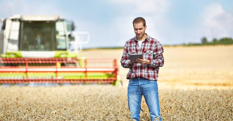 farmer in field holding tablet computer