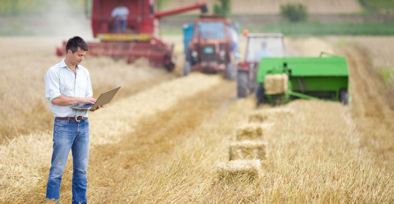 farmer on laptop in field during harvest_FDS_Jevtic_iStock_Getty Images-512008841.jpg