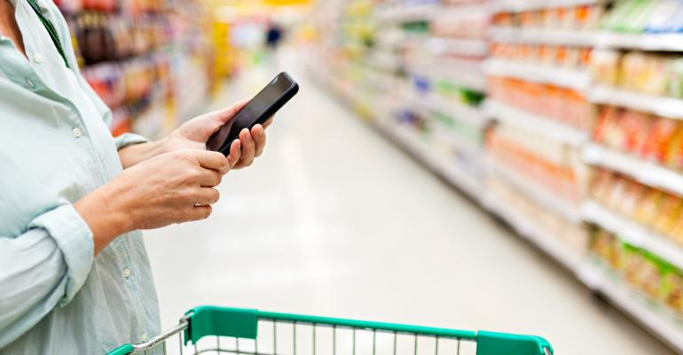 woman grocery shopping while on mobile phone
