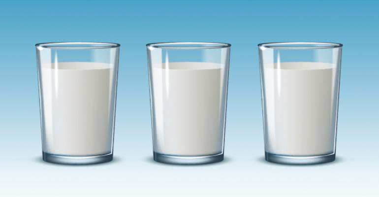 three glasses of milk on blue background