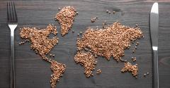 global map representing world hunger or food security on wood table with knife and fork