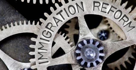 Macro photo of tooth wheel mechanism with IMMIGRATION concept words